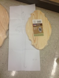 Checking how the full sized sketch of the dagger looks next to the pre-made plaque for proper sizing.