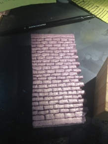 I scribed a brick pattern into pink insulation foam.